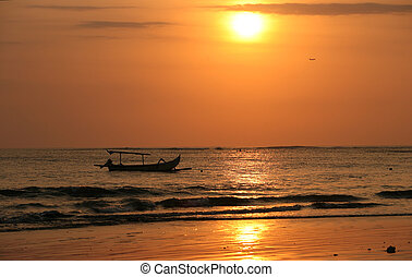 Drifting boat on a sunset Coast of the Indian ocean Bali