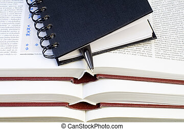 Notebook and Pen on Books - a notebook and a pen lying on...