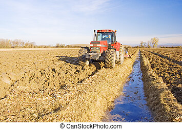 Ploughing - Tractor ploughs the land