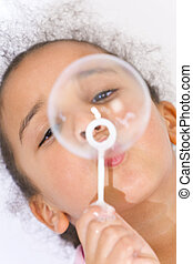 Blowing Bubbles - A beautiful young mixed race girl blowing...