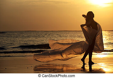To fly for me - The beautiful woman on a coast on a sunset