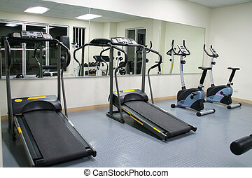 exercise gym with large mirrors, treadmills and stationary...