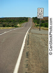 Drive on left in Oz - A road sign in the outback that warns,...