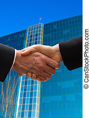 The Deal - hand shake outside in front of a business...