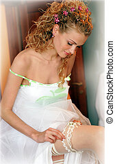 Bride pulling on her garter - Smiling bride in a traditional...