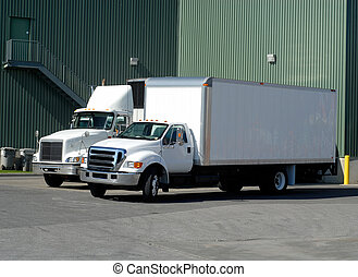 Delivery Trucks - Two White Delivery Trucks Backed Up to A...
