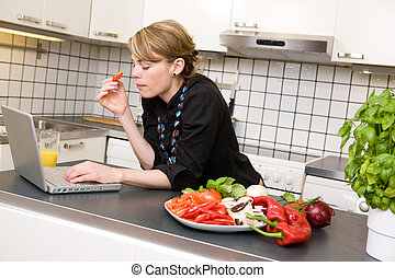 Surfing in the Kitchen - A young business woman surfs the...