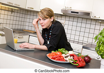 Lunch in Kitchen with Laptop - A young female woman using...