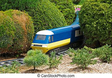 model train - a model train goes through a countryside rural...