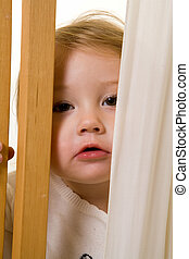 Peek-a-boo - Face of an adorable caucasian blond baby girl...