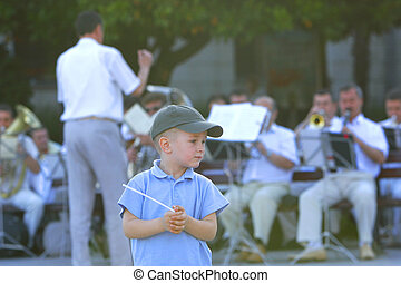 young conductor on orchestra background