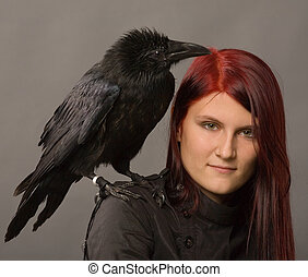 witch - young woman with black raven on gray background