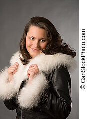 woman in fur coat - young woman in fur coat on gray...
