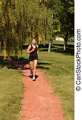 Runner - Young woman jogging through the park