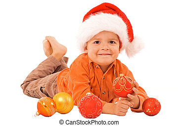 Boy in santa hat laying among christmas baubles - isolated