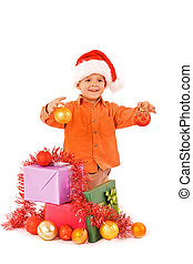 Boy in santa hat with christmas baubles and presents - isolated with a bit of shadow