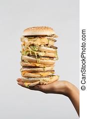 Want a Bite - A massive burger held out on a hand