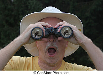 Bird Watcher - Man looking at a Bald Eagle through...