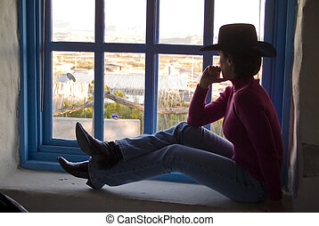 Gazing out the Window - A woman in western apparel sitting...