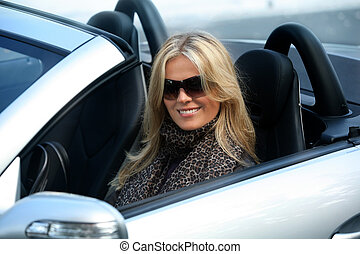 Blond girl in a car - Blond girl in sunglasses driving...