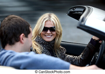 Couple in the car - Blond woman and a man in a convertible...