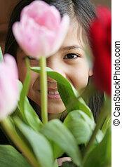 Child peeking thru flower while playing