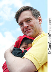 Safe and sound with Dad - Baby boy cuddled safely in his...