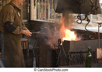 Blacksmith - A blacksmith working at an old iron forge