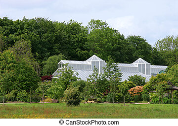Greenhouse Splendour - Large white greenhouse set amidst...