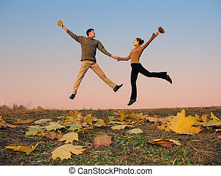 jump couple autumn leaves sunset sky