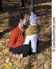 mother with baby sit on many autumn leaves