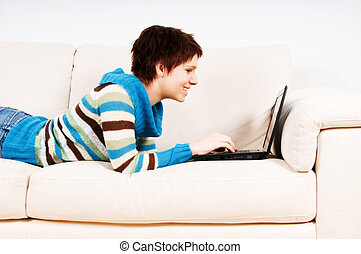 Laptop time - cute woman on her couch with her laptop