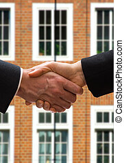 Hand Shake - business hand shake in front of a brick...