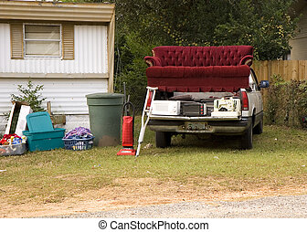 Trailer Trash - Trash and old furniture on a truck and next...
