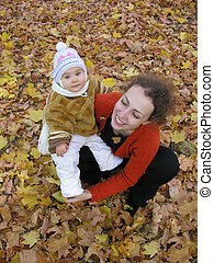 mother with baby on autumn field from up