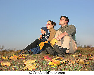 family sit with autumn leaves