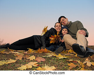 family with autumn leaves and sunset