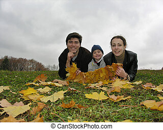 smile faces of family on autumn leaves
