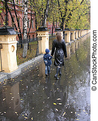 mother walking with son. autumn . rain