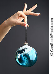 new year ball - The hand gives the new year ball on a black...