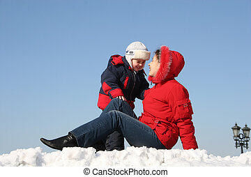 mother sit with son. winter