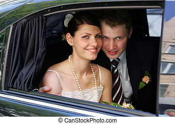 Bride and Groom in wedding limousine - A newly married man...