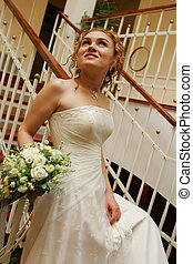 Bride with bouquet  walking down stairs
