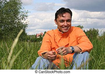 man sit on meadow