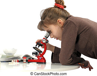 Girl and microscope - Girl peers into microscope studies...