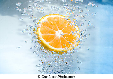 Tangerine slice in blue  water with air bubble.