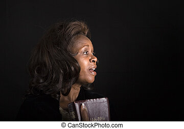 LR1 Diane Singing - A black woman with bible in hand singing...