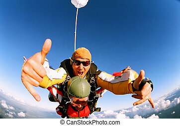 Skydiver giving the thumbs up - A tandem skydiver giving the...