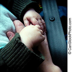Hands of Baby in Car Seat - Detail of Hands: Baby Strapped...