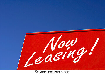 Now Leasing - A bright red Now Leasing Sign against blue sky...